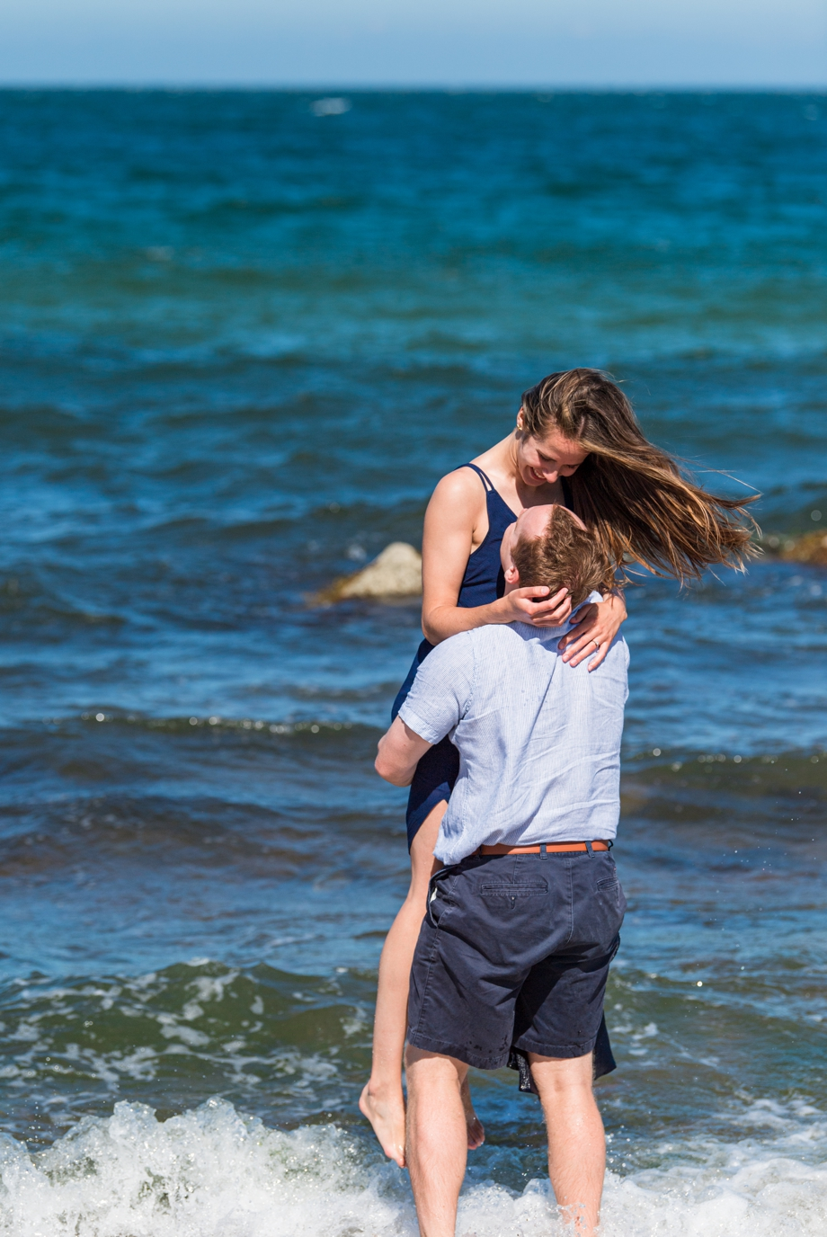 engaged couple dancing on the beach