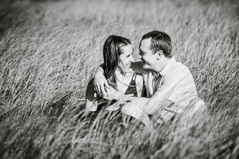 Black and white photo of couple sitting in beach grass