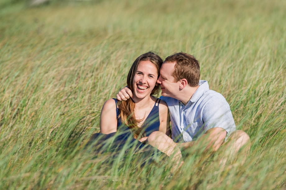 Engaged couple sitting in beach grass