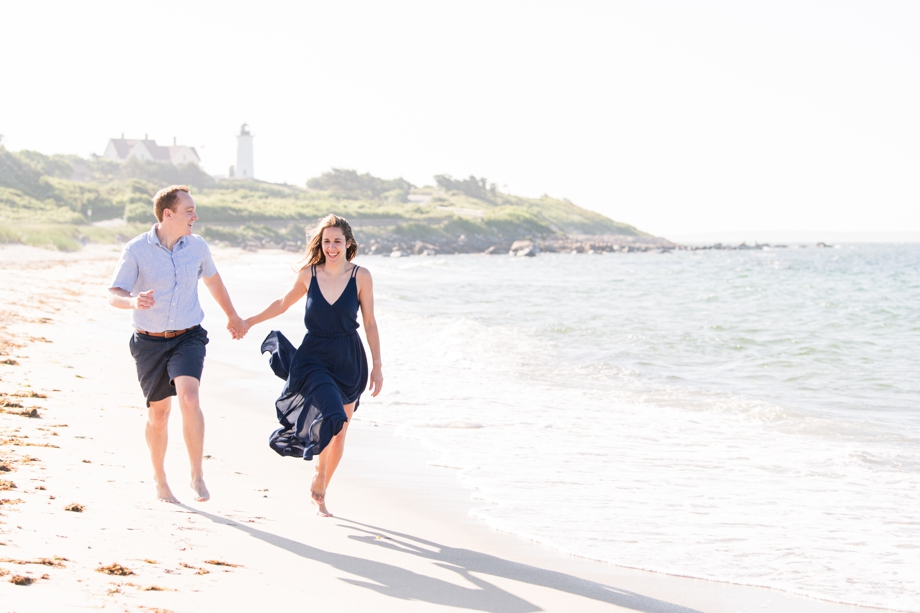 Engaged couple running on beach with nobska lighthouse in the background