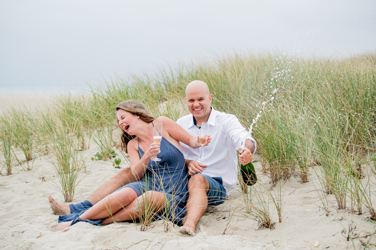 Engaged couple popping champagne on Ridgevale Beach on Cape Cod