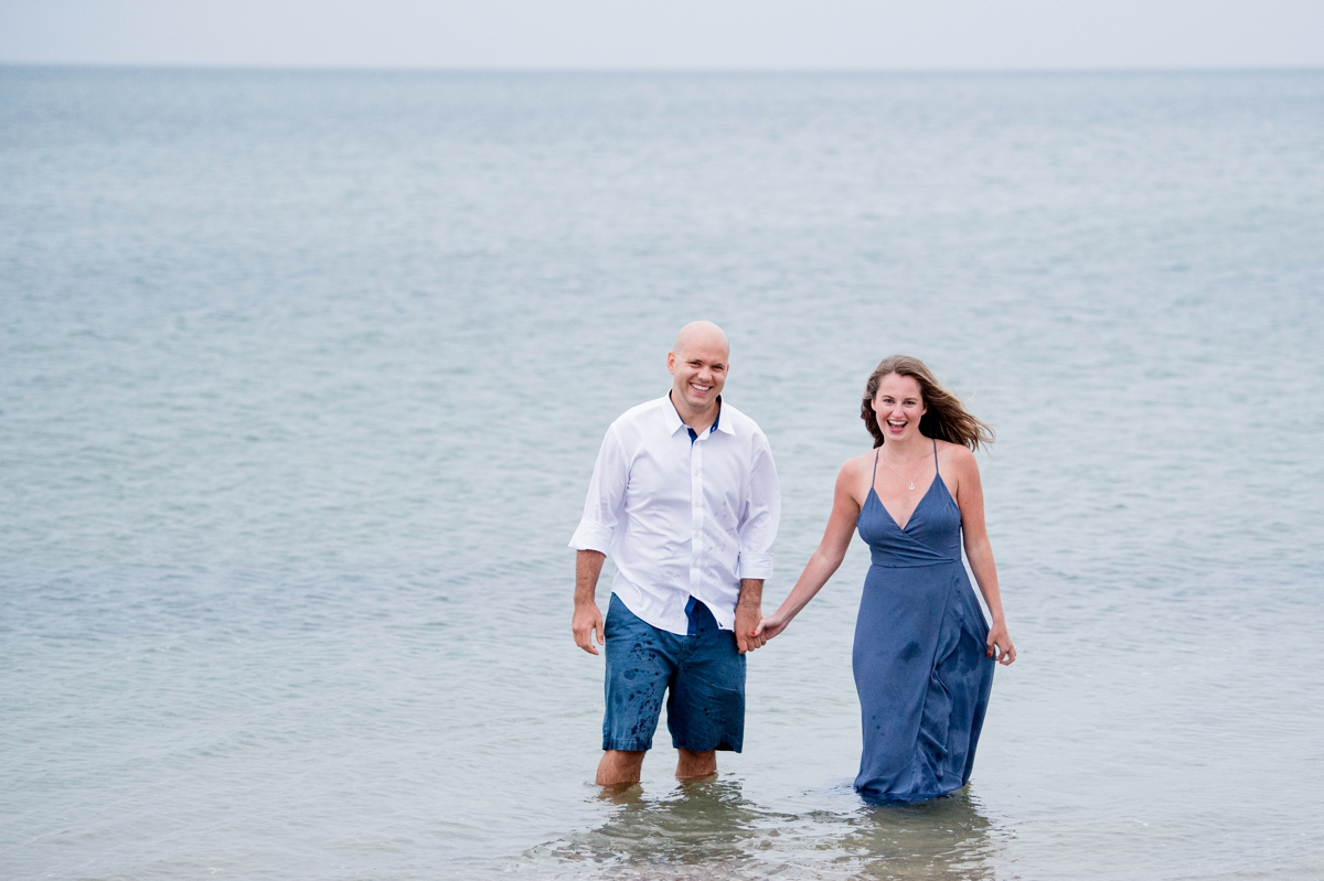 Engaged couple standing in water Ridgevale Beach on Cape Cod