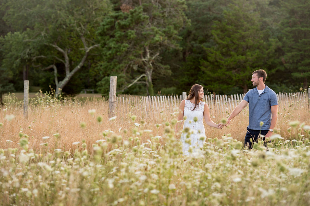 Couple holding hands through meadow. What to Wear for Engagement Photos
