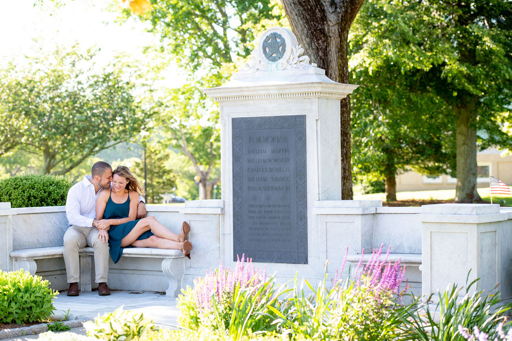 Couple sitting next to monument. Lady in navy dress, man in white shirt and beige chinos. What to Wear for Engagement Photos