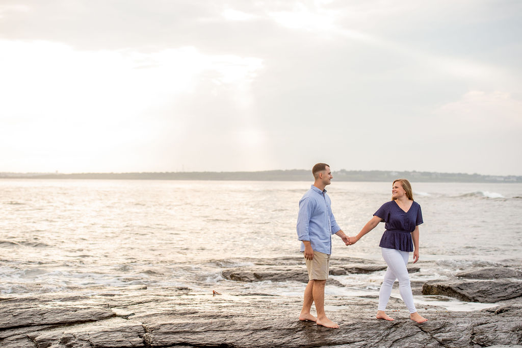 Couple holding hands on the shore I What to Wear for Engagement Photos