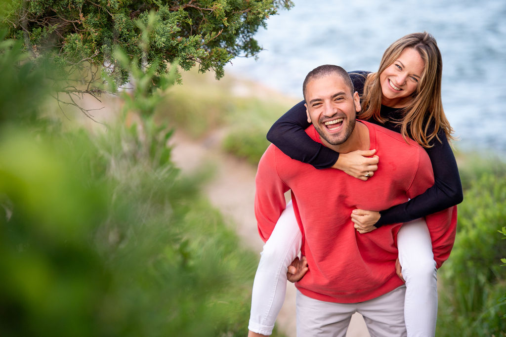 Man in bright red sweater carrying his fiance on his back up from the beach I What to Wear for Engagement Photos