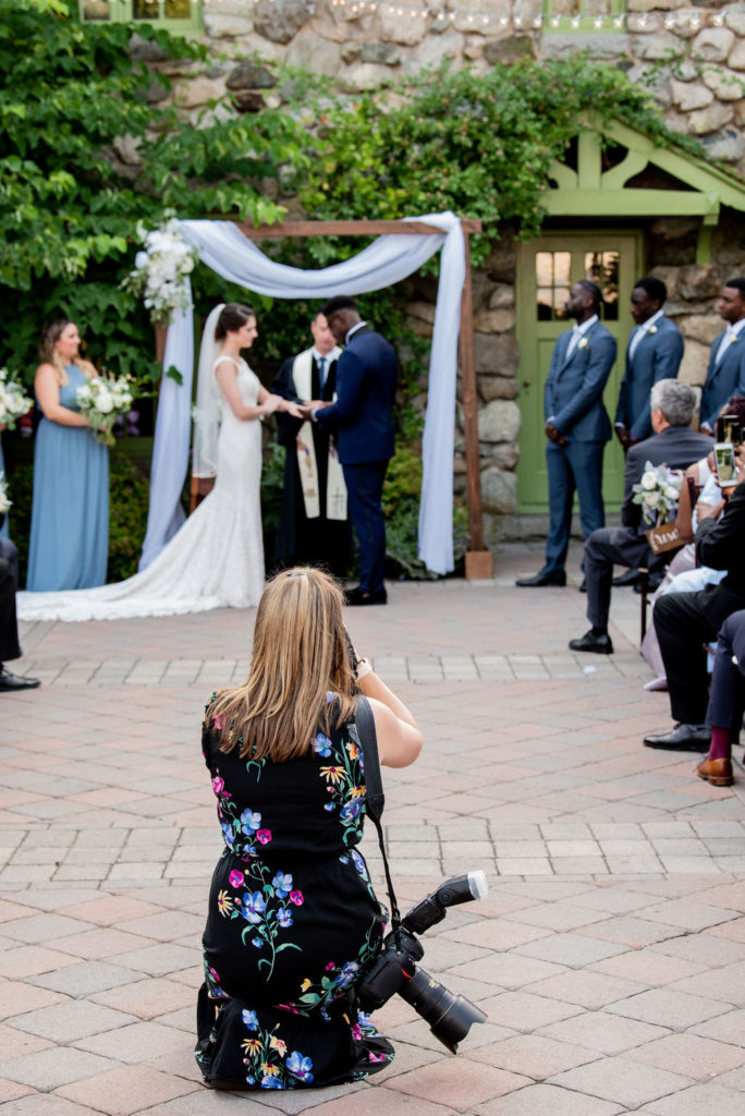 Alicia kneeling at the end of the aisle taking photos of a couple getting married I Questions to ask your photographer